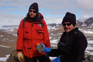 تام تابین و همکارش که فسیل یک شکم پا را در دست دارد